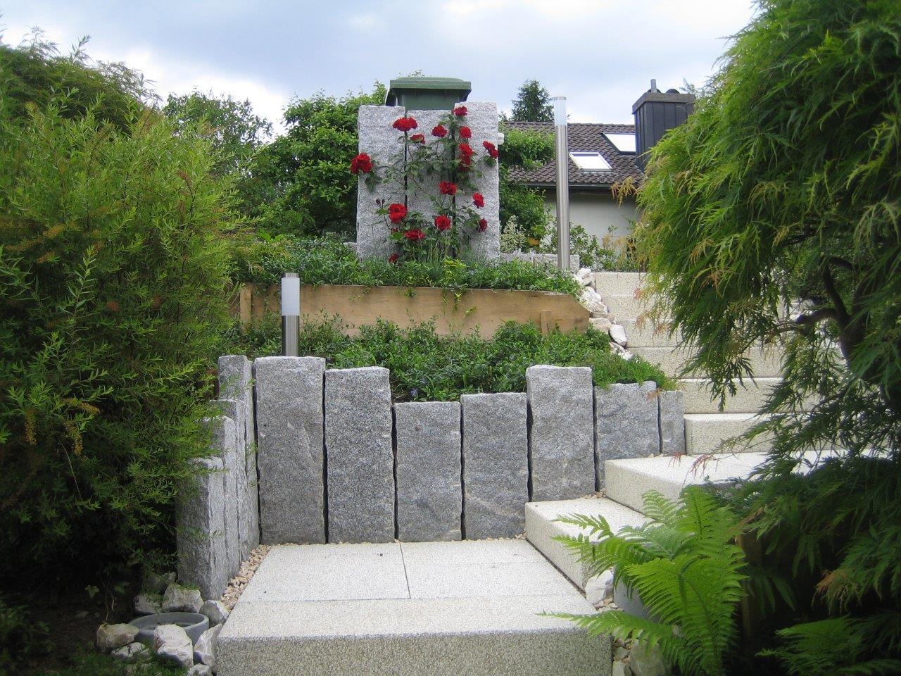 Neugestaltung Eingangsbereich: Hangabschluss mit Granitstelen, Gartenplatten und Blockstufen jurasplitt gelb