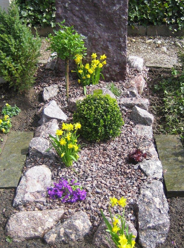Grab-Gestaltung mit Natursteinen und Polsterpflanzen